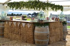 As the previous owner of Devon Vintage China, I  designed this rustic bar using hay bales, barrels & trestle table-tops & hung hop garlands from a frame. Barrels can be hired from South-West Event Hire.