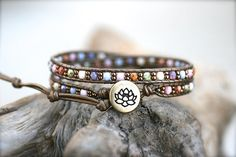 This beautiful leather wrap bracelet is made with bronze seed beads, multi color czech glass beads woven on metallic bronze leather cord. Antique bronze lotus flower button with 3 adjustable loop closures. Stylish, versatile and well made. Bracelet wraps around wrist 2x. Bracelet size: 6.5- 7