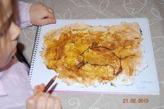 La imagen se corresponde con una actividad relacionada con el tema de la prehistoria. Se lleva a cabo mediante la utilización de un folio blanco que se pinta con acuarela de un anaranjado y cuando esta seco, los niños dibujan una imagen prehistórica. A continuación, mediante el uso de distintas especias crean sus propios pigmentos y pintan empleando sus dedos