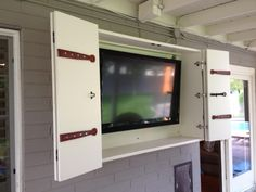 Exterior. Out Door Wall TV Cabinet With Bi Fold White Painted Wooden Door.  Shocking
