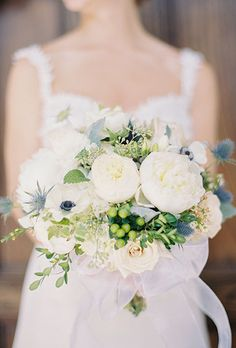 Brides.com: . A classic white peony bouquet accented with anemones, thistle, and berries, created by Acorn Home & Garden.