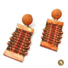 """Arosdonde el protagonista absoluto es una pequeña pieza tejida a telar. Gabriela Casteránrescata estatécnica para honrar nuestros orígenes. De un tope metálico se suspende la pieza a telar.El brillo del metal se contrapone a la calidez de las fibras de tonos terracota en los que sedistingue un diseño en el centro. Estos aros son parte de la colecciónNahuenque alude al fonema Newen que significa """"Energía""""enMapudungún. El arte textil mapuche data de tiempos precolombinos y…"""