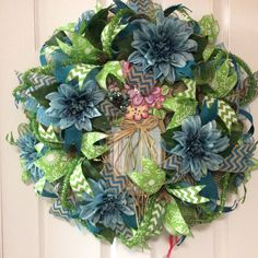 """""""Lime and Blue Dahlia Wreath"""" This wreath is great to start the spring with and take you right into summer! It is 28""""x28""""x8"""" deep, on a pencil burlap wire frame, burlap deco mesh, blue/moss green deco mesh curls, green tinsel tubing woven throughout, center wood embellishment, blue silk dahlias with greenery, 2.5"""" burlap/blue chevron ribbon, 2.5"""" green burlap floral print ribbon, 1.5"""" green/white chevron ribbon, 1.5"""" blue cotton ribbon.  If interested, please message me. Thank you."""
