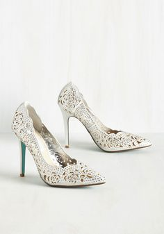 Sashaying to your seat in these opulent pumps by Betsey Johnson, your luxe look gives this fine dining experience extra stars. Glistening with rhinestones atop a sparkling silver textile, this posh pair continues to wow with pointed toes, scalloped edges, and rose-shaped cutouts.