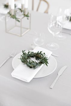 Throw An All White Party With These Ideas For Food And Decorations / Create a simple white table setting with a white cloth napkin, gold accents and a mini plant wreath.