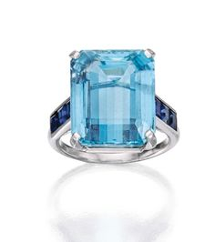 PLATINUM, AQUAMARINE AND SAPPHIRE RING, CARTIER, FRANCE Centering an emerald-cut aquamarine weighing approximately 13.75 carats, flanked by six calibré-cut sapphires, size 7½, signed Cartier, indistinctly numbered, with French assay mark.