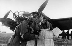 German crew look at a map in preparation for flight in front of a Heinkel He III