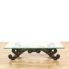This coffee table is featured in a solid wood with a glossy chestnut finish. This traditional style cocktail table has a rectangular glass top, intricately carved base, and center floral motif. Perfect for holding and serving drinks! #americantraditional #tables #coffeetable #sandiegovintage #vintagefurniture