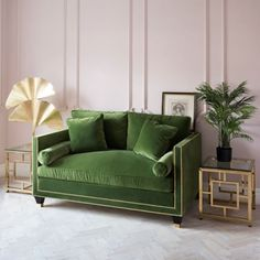 Leafy green sofa with blush sugary pastel pink walls. Painted panelling. Tropical and boho style for the home. Quirky interior design.
