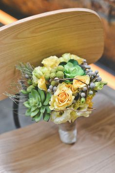 Beautiful bouquet of yellow roses and green succulents with touches of purple