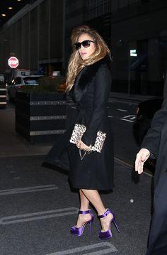 Jennifer Lopez looking fabulous in purple heels and black coat.