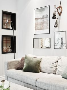 Small gallery wall in living room above neutral sofa