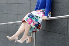 a blue sweater with floral skirt and nude tights + nude heels.