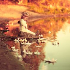 AnnaGrazhdankina has created an extraordinary photograph, of a child that is captured almost spontaneously, playing with paper boats.