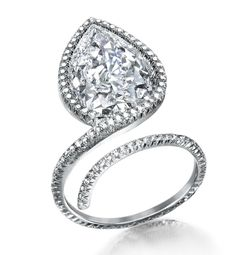 Centering a pear-shaped diamond weighing 5.04 carats, with additional pavé set diamonds. Mounted in platinum.