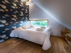 Acquario | Penzion Zikmundov A beautiful room where you wake up with an amazing view of the Buchlov castle and surrounding forests. Hand-printed wallpapers with Verne's fish motives by the Italian painter Piero Fornasetti evoke the romance of Karel Zeman's movies. #zikmundov #room #pension #interior #bed