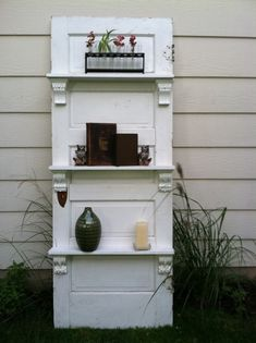 Turning an old door into a bookcase. I love the carved corbels used as supports for the shelves!