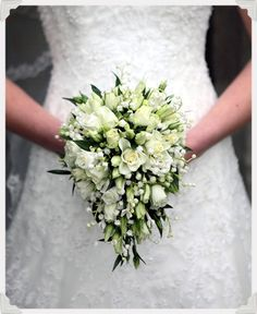 Nice colours, round though  ivory teardrop bouquet of avalanche spray roses, ivory lisianthus, white bouvardia and lily of the valley