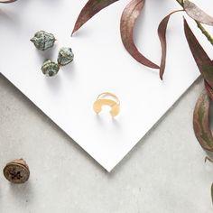La pieza es una circunferencia abierta, plana, con dos marcas centrales en bajorrelieve y la base está colocada de forma que no se vea y rompa la estética del anillo