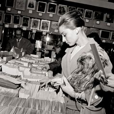 Hepburn leafs through postcards with Mr. Famous, December 21, 1959.