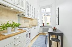 wąska biała kuchnia w stylu skandynawskim z czarnym stołem i metalowymi taboretami - Lovingit.pl