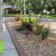 Flowerbed with rocks, stones, grasses, large pot on side.