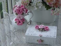 This tea pot is silver it is spray a shabby white then adorned with my handmade shabby roses and vintage brooches and  some dripping pearls.  the other is a jewlery box  marjorie _ gls @ yahoo.com