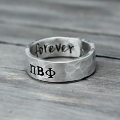 This custom Pi Beta Phi sorority ring is the perfect way to show of your letters. ♥ 14 gauge aluminum ♥ Infinity heart stamp on the outside edge ♥ Outside stamped with your letters