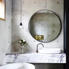 Concrete walls and a marble vanity? Consider us sold. The mix of high and low materials is edgy yet refined. We also love the use of a large round mirrorand single bubble pendant.