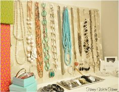 hang necklaces on a piece of foam board covered in decorative paper from a push pin.  This keeps the necklaces untangled and in plain sight.