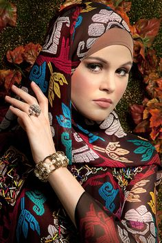 Red printed chiffon kaftan and shawl by Kamila by Itang Yunasz. Gold pearl bracelet and silver floral ring by Donini Accessories.