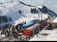 Winter scenery at the upper station Rigi Kulm (1750 meters over sea level): the red train came from Vitznau, the blue one is a sport train for sportspersons with sledgs. The peak with the ski slopes in the background is called Rigi Rotstock