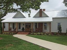 This charming white farmhouse-style home, belonging to Chip and Joanna Gaines of HGTV's Fixer Upper, features a generous porch and a wide front lawn.