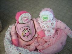 Baby shower gift for twins.  I made this for my cousin Courtney!  Twins are made from rolled newborn diapers that you stuff into the outfit.  Mom gets diapers, outfits, bibs, hats, pacifiers, mittens & blankets.  Cute alternative to a diaper cake!