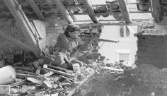 British Sniper 4, WWII, House-to-house fighting became a matter of routine in the days following D-Day. A British sniper takes refuge in a loft and watches for movement. Snipers wore what suited them and this man carries the practical and large Bren-gun magazine pouches instead of small ammunition pouches, as well as carrying a pistol on his hip.