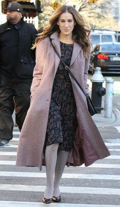 Sarah Jessica Parker wears a printed dress with a dusty-pink coat, gray tights and a black crossbody bag.