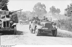 Soldiers of 11. Panzer-Division passing a Soviet BA-10