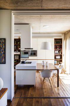 Cocina comedor integrada a un playroom y al living en forma armónica, con líneas simples y acentos en blanco y madera. La isla con las hornallas se expande a una mesa para compartir.