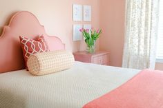 Coral bedroom features coral headboard on full bed dressed in white quilt, pink blanket, white and orange bolster pillows and orange trellis pillow leaning against peach colored walls next to art gallery over soft pink painted nightstand.