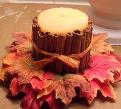 bricolage automne - arrangement original d'une bougie blanche décorée de bâtons de cannelle, ruban raphia et feuilles automnales décoratives