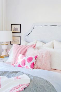 Pink and white bedroom with pink pillows and gray bedding