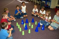"Rhythm Game ~ The green cups are rests or ""shhh"" notes. The blue cones are quarter notes. The children help move the cones around the cups to create patterns they like, then ""read"" the patterns by clapping and resting. First graders really enjoyed this activity and were able to pick up some composition grids and create their own patterns on paper."