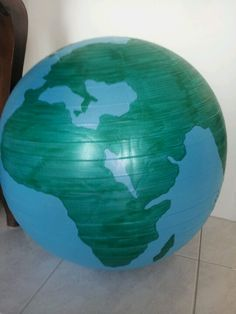 Use green artline to draw the world onto a blue fitness ball.
