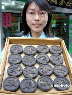 tray of round tea bricks of compressed tea leaves, embossed with Chinese characters