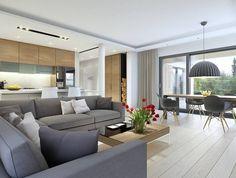 canapé gris, chaises design Eames noires avec pieds en bois et parquet clair