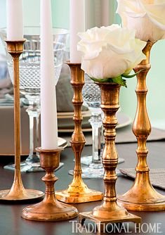 Topped with white taper candles and white roses, an assortment of mismatched brass candlesticks casts a flickering glow down the center of the table. - Photo: Michael Garland