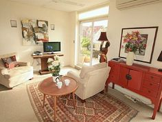 Bondi Beach, Australia vacation apartment rental - Living room with white furniture, tribal rug, and Asian inspired console cabinet