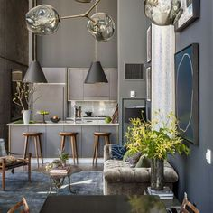 Is it a club? Is it a bar? Who cares when it's this fabulous. This kitchen is begging for a lively get-together under these stunning Tom Dixon lights. A shimmering grey velvet sofa, brass-edged cabinetry and luxe accessories add pure hotel-chic to the space.