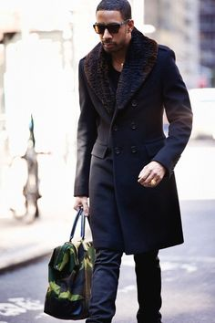 This combination of a black fur collar Сoat and navy jeans is perfect for a night out or smart-casual occasions. Shop this look for $870: http://lookastic.com/men/looks/tote-bag-crew-neck-sweater-sunglasses-jeans-fur-collar-oat/4922 — Dark Green Camouflage Canvas Tote — Black Crew-neck Sweater — Dark Brown Sunglasses — Navy Jeans — Black Fur Collar Сoat