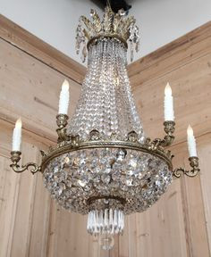"Neoclassical inspired chandelier. Boasting an intricately cast brass framework that includes also some baroque embellishment around the rim and acanthus plumes forming a crown at the top, this elegant French chandelier has been lavished with abundant multifaceted crystals in the classic ""sack of pearls"" design, making its elegance stand out above the rest."